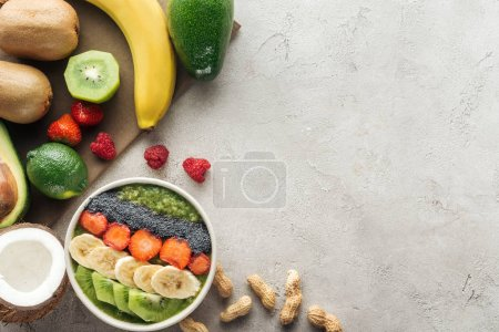 Photo for Top view of smoothie bowl with fresh fruits and nuts on grey background - Royalty Free Image