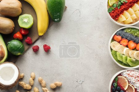Photo for Top view of colorful smoothie bowls with ingredients on grey background - Royalty Free Image
