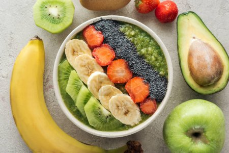 Photo for Top view of delicious smoothie bowl with fresh fruits and ingredients on grey background - Royalty Free Image