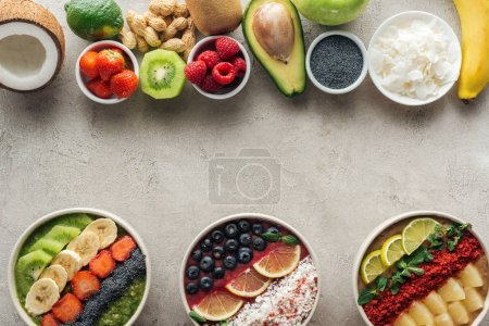 top view of smoothie bowls with ingredients on grey background