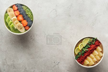 Photo for Top view of healthy organic smoothie bowls with fruits on grey background with copy space - Royalty Free Image