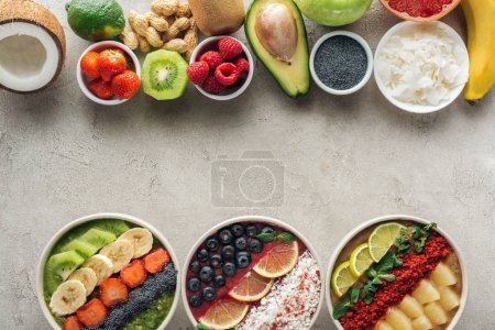 Photo for Top view of smoothie bowls with ingredients on grey background - Royalty Free Image