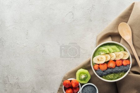 Photo for Top view of smoothie bowl, wooden spoon and ingredients on grey background with copy space - Royalty Free Image