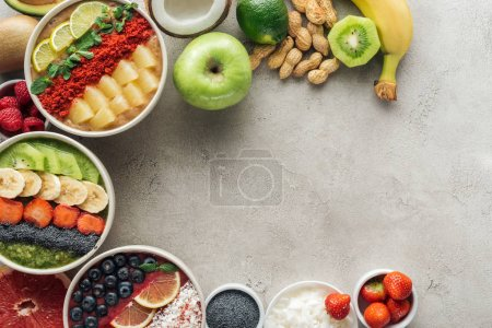 Photo for Top view of smoothie bowls with ingredients on grey background with copy space - Royalty Free Image
