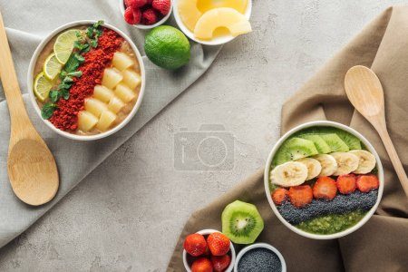 Photo for Top view of delicious smoothie bowls with ingredients on tablecloths - Royalty Free Image