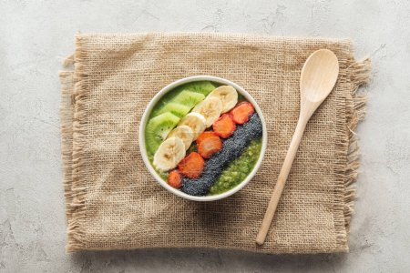 Photo for Top view of fresh smoothie bowl on sackcloth with wooden spoon - Royalty Free Image