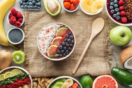 Photo for Top view of smoothie bowls with wooden spoon and frame made of fresh ingredients on sackcloth - Royalty Free Image