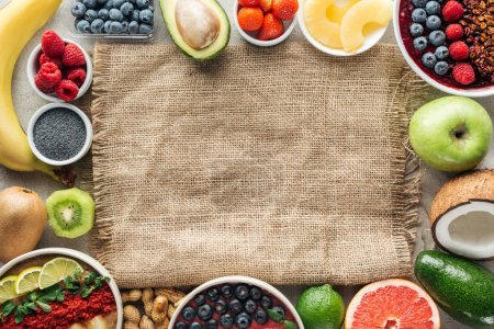 Photo for Top view of frame made of smoothie bowls and fresh ingredients on sackcloth with copy space - Royalty Free Image