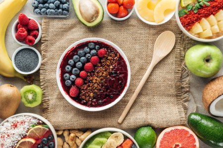 Photo for Top view of smoothie bowls and frame made of fresh organic ingredients on sackcloth - Royalty Free Image