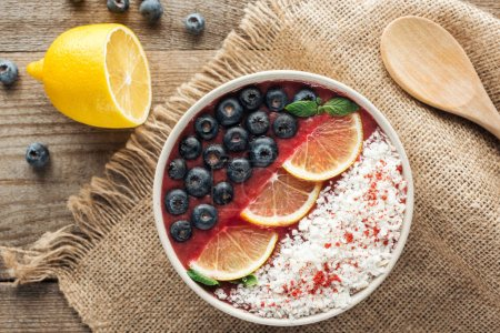 Photo for Top view of healthy organic smoothie bowl with blueberries, lemons and shredded coconut on sackcloth - Royalty Free Image
