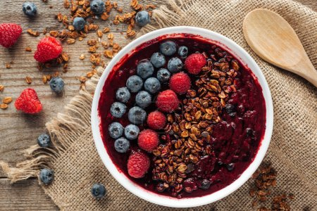 Photo for Top view of delicious organic smoothie bowl with berries and granola on sackcloth - Royalty Free Image