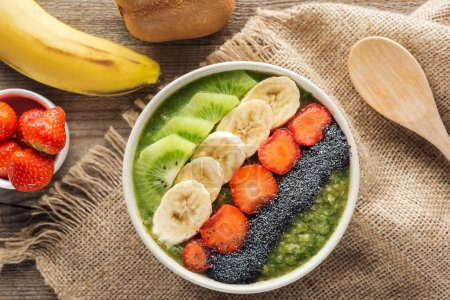 Photo for Top view of fresh smoothie bowl with ingredients on sackcloth - Royalty Free Image