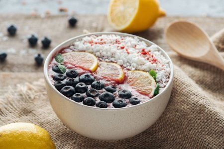 Photo for Selective focus of smoothie bowl with fresh fruits on sackcloth - Royalty Free Image