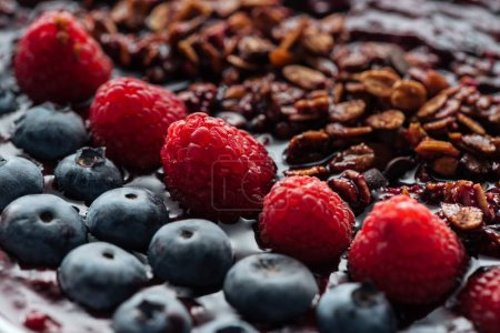 Photo for Selective focus of blueberries, raspberries and homemade granola in smoothie bowl - Royalty Free Image