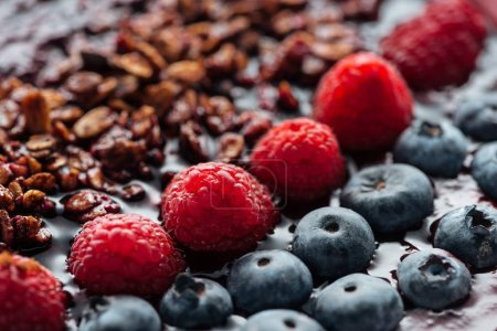 Photo for Selective focus of blueberries, raspberries and granola in smoothie bowl - Royalty Free Image
