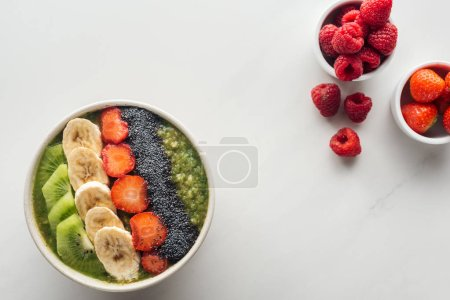 Photo for Top view of smoothie bowl with fresh fruits on white background - Royalty Free Image