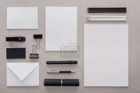 Photo pour Lay plat avec papeterie noir et blanc au milieu sur fond gris - image libre de droit