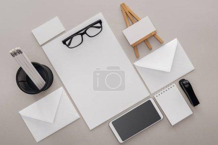 Photo pour Lay plat avec cartes vierges, lunettes, smartphone et papeterie sur fond gris - image libre de droit