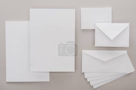 Photo for Top view of white empty papers and envelopes on grey background - Royalty Free Image