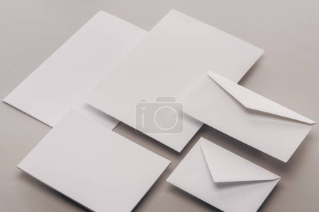 Photo for Flat lay with empty white papers and envelopes on grey background - Royalty Free Image