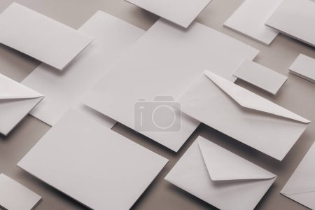 Photo for Close up of empty white papers and envelopes on grey background - Royalty Free Image