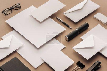 Photo pour Verres, feuilles de papier, stylo, cahier, cartes, agrafeuse sur fond beige - image libre de droit