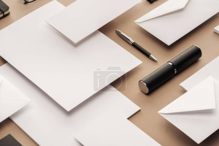 Foto de Pluma, caja, sobres y hojas de papel sobre fondo beige - Imagen libre de derechos