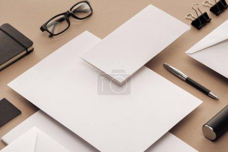 Photo pour Pose plate avec lunettes, stylo, carnet, étui, trombones, enveloppes et feuilles de papier - image libre de droit