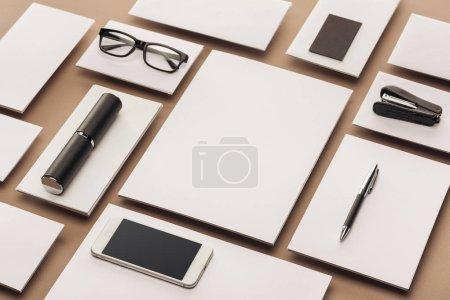Foto de Hojas vacías, caso, gafas, smartphone, pluma y grapadora sobre fondo beige - Imagen libre de derechos