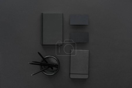 Photo for Top view of pencils, notebooks and cards  on black background - Royalty Free Image