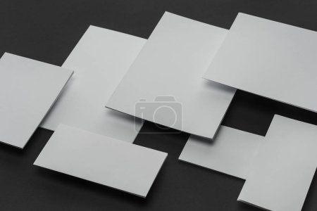 Photo for Flat lay with white sheets of paper and cards on black background - Royalty Free Image