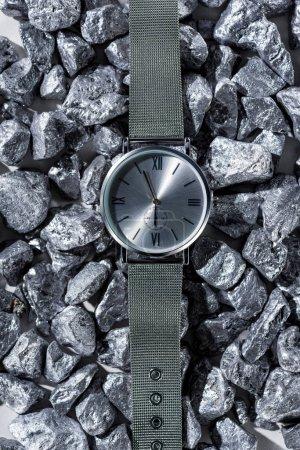 Photo pour Vue de dessus de montre métallique avec horloge mains sur pierres - image libre de droit
