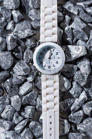 Photo pour Vue de dessus de montre blanche avec horloge mains sur pierres - image libre de droit