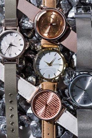Photo pour Vue de dessus des montres élégantes allongé sur les pierres grises - image libre de droit