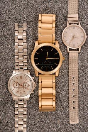 Photo pour Vue de dessus des montres de luxe allongé sur le sable doré - image libre de droit