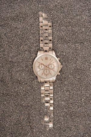 Photo pour Vue de dessus de montre-bracelet or couché sur le sable - image libre de droit