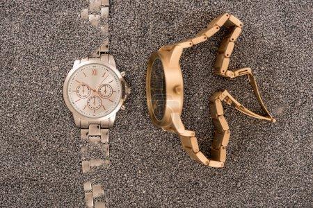 Photo pour Vue de dessus des montres-bracelets allongé sur le sable doré - image libre de droit