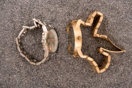 Photo pour Vue de dessus des montres-bracelets allongé sur le sable - image libre de droit