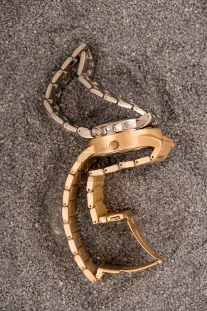 Photo pour Vue de dessus des montres de luxe or couché sur le sable - image libre de droit