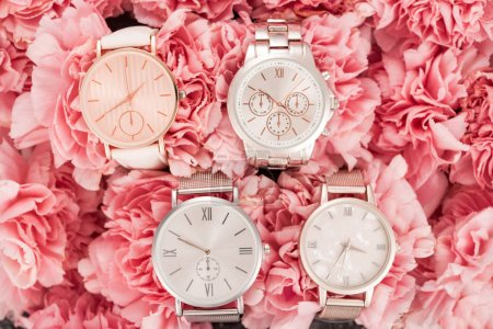Photo pour Vue de dessus des montres-bracelets couché sur des fleurs floraison roses - image libre de droit