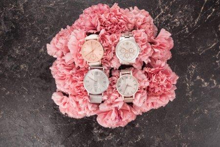 Photo pour Vue de dessus des montres-bracelets élégants couché sur des fleurs fleurs roses sur la surface grise - image libre de droit