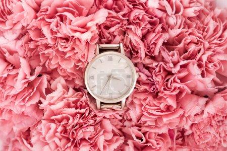 Photo pour Vue de dessus de montre-bracelet Suisse de luxe couché sur des fleurs épanouies - image libre de droit