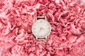 top view of luxury swiss wristwatch lying on blooming flowers