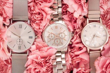 Photo pour Vue de dessus des montres-bracelets couché sur oeillets floraison roses - image libre de droit