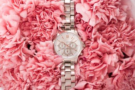 Photo pour Vue de dessus de montre-bracelet élégant couché sur des fleurs épanouies - image libre de droit