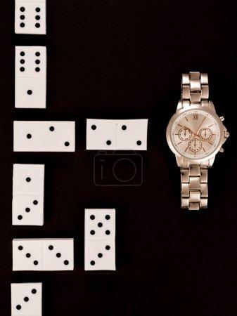 Photo pour Vue de dessus de montre-bracelet de luxe se trouvant près de dominos isolés sur fond noir - image libre de droit