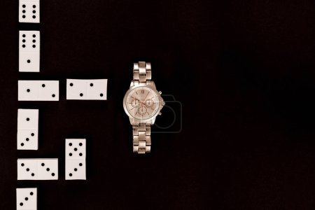 Photo for Top view of luxury wristwatch lying near dominoes isolated on black - Royalty Free Image