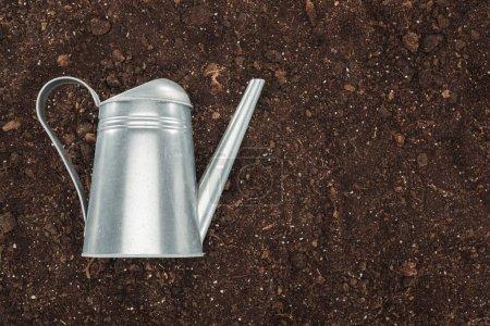 Photo pour Vue du dessus de l'arrosoir sur le sol, la protection de la nature concept - image libre de droit