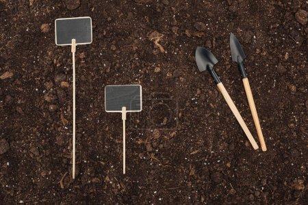 Photo pour Vue de dessus des plaques vierges près des pelles sur le sol, la protection de la nature concept - image libre de droit