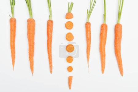 Photo for Top view of composition with whole carrots with one sliced carrot in center isolated on white - Royalty Free Image